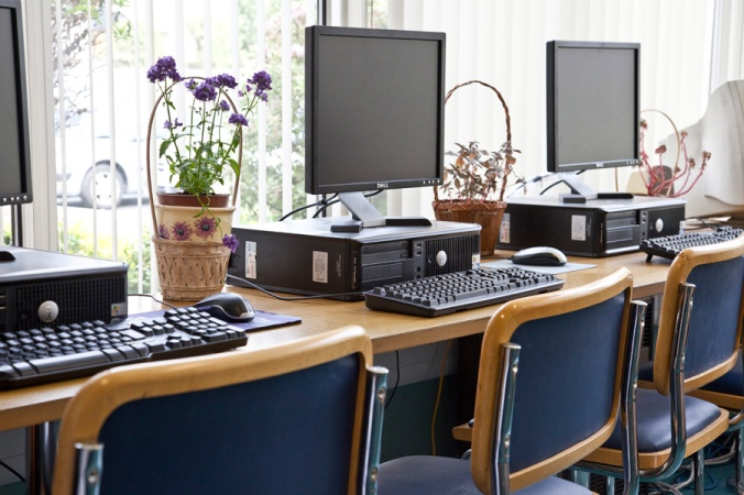 Image of three computers and potted plants on desks with chairs in foreground. Location: St. Michael's Hospital Library.
