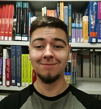 Picture of Jesse Waters in front of library shelves.