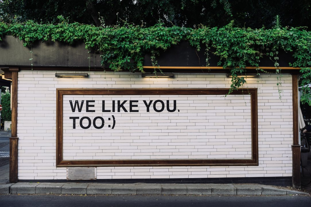 black text painted on white brick wall outside: we like you too :)